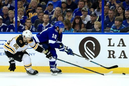 J.T. Miller (R) of the Tampa Bay Lightning and Kevan Miller of the Boston Bruins fight for the puck
