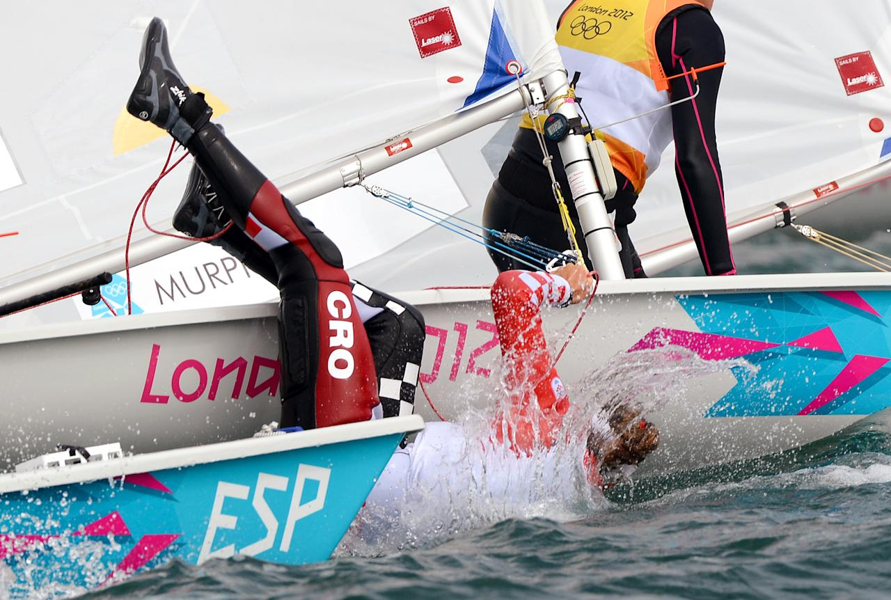 Croatia's Tina Mihelic falls from her dinghy in the Laser Radial sailing class at the London 2012 Olympic Games, in Weymouth on August 3, 2012.  AFP PHOTO / William WEST
