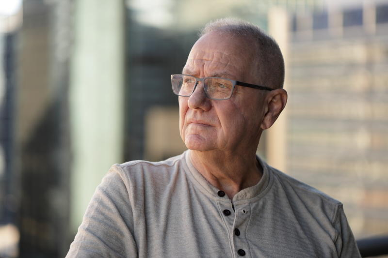 Senior man with facial scar looking to the side. Out of focus office buildings in the background.