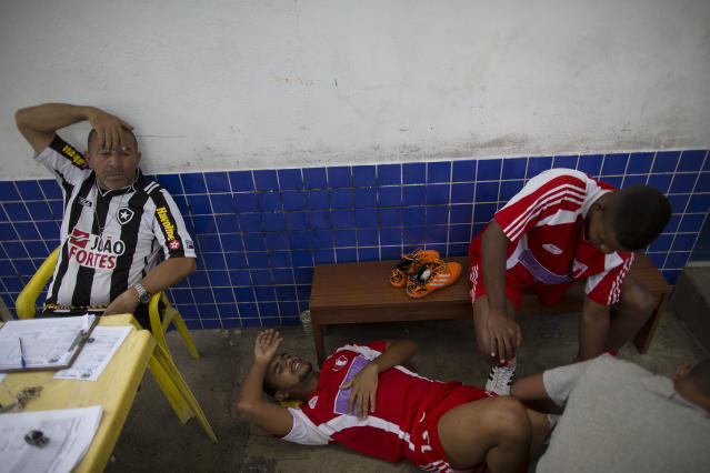 In this April 27, 2014 photo, Bayer's Vagner Vieira, 25, lies on the floor as he is attended by teammates after he was injured at an amateur soccer match in the Vila da Penha neighborhood of Rio de Janeiro, Brazil. Brazil is a five-time champion of the World Cup, and will host this year's international soccer tournament starting June 12. In Brazil, soccer is a unifying force. (AP Photo/Leo Correa)