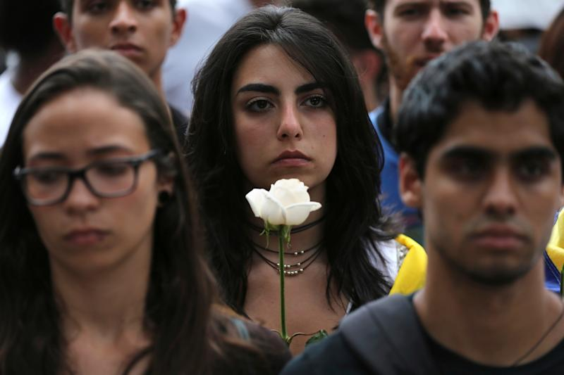 A protester carries a white flower during a silent protes - Credit: Fernando Llano/AP
