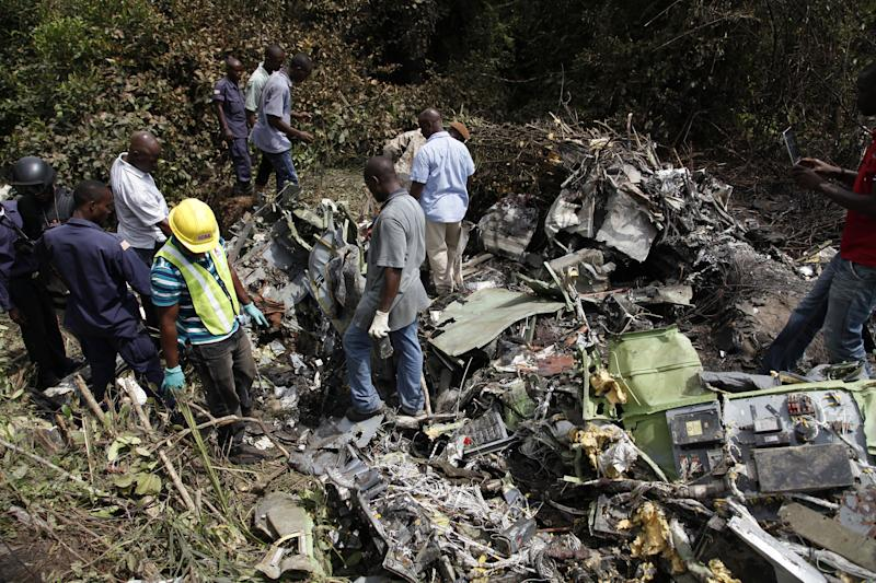 Rescue workers inspect the wreckage of a military plane that crashed near Monrovia, Liberia, Monday, Feb. 11, 2013. Eleven bodies were pulled from the debris, with Guinea's army chief of staff and top military officers among its passengers, officials said Monday.(AP Photo)