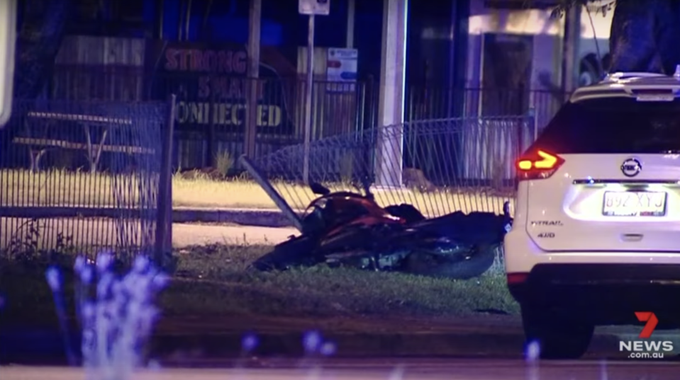 A motorbike sits on grass in Townsville after a fatal crash.