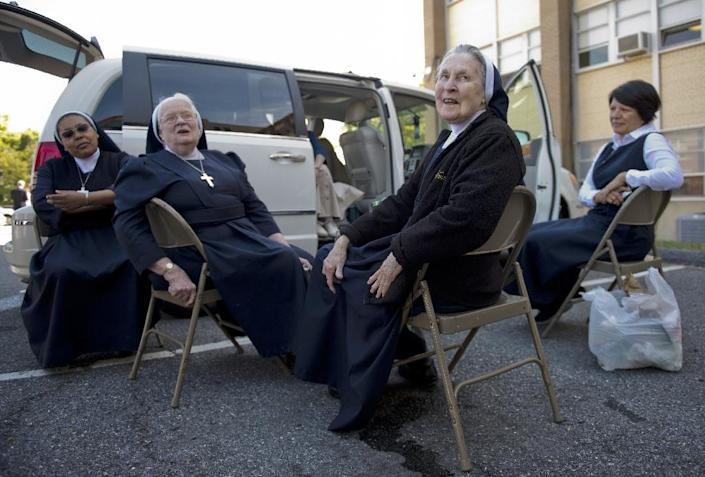 A group of nuns have a picnic near their van as they wait for the arrival of Pope Francis at the Basilica of the National Shrine of the Immaculate Conception in Washington, DC on September 23, 2015 (AFP Photo/Andrew Caballero-Reynolds)