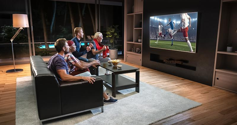 A family sits in a living room watching soccer on a big screen TV.