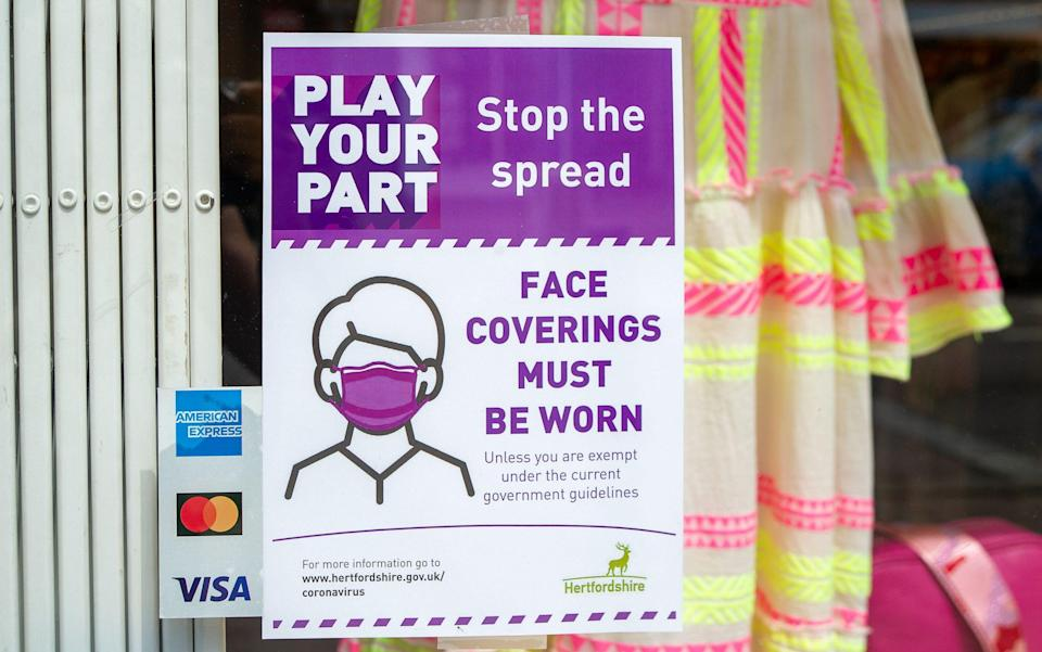 Most shop owners have left Covid-19 Face Coverings signs in their windows although the wearing of face masks in shops is no longer a legal requirement in England - Maureen McLean/Shutterstock