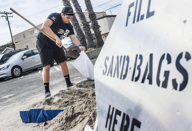 Chad Adriano fills up sand bags before the weekend storms at the Orange County Fire Authority Station 44 in downtown in Seal Beach, Calif., Thursday, Feb. 16, 2017. Wet weather returned to California on Thursday with the first in a new series of rainstorms moving across the northern half of the state while the south awaited a storm that forecasters said could be the strongest in years if not decades. (Nick Agro/The Orange County Register via AP)