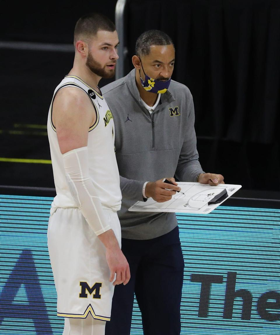 Michigan's Hunter Dickinson listens to head coach Juwan Howard during last Saturday's game against Ohio State at Lucas Oil Stadium in Indianapolis.