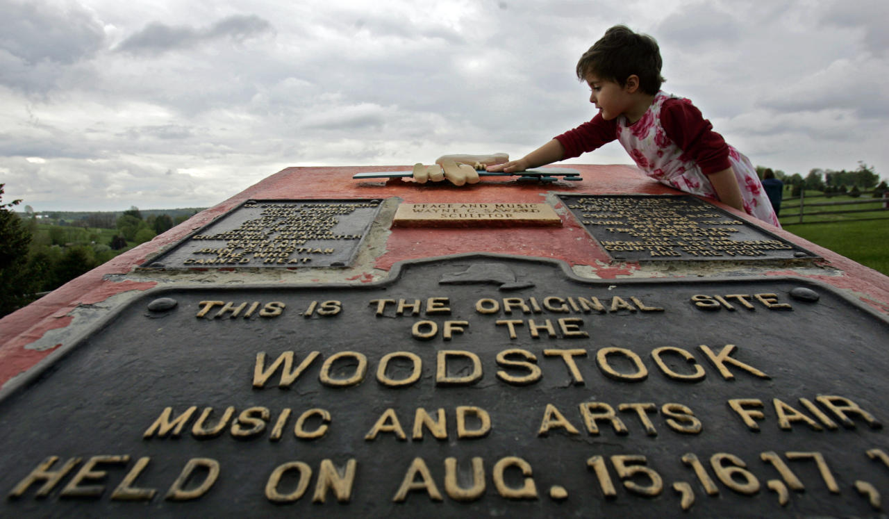 """FILE - This May 15, 2008 file photo shows Emma Cenholt, 3, of Trumbull, Conn., playing on a memorial at the site of the Woodstock Music and Arts Fair in Bethel, N.Y. Woodstock 50 is less than four months away, but tickets for the event are still unavailable. Tickets for the three-day festival on Aug. 16-18 were supposed to go on sale Monday. The festival released a statement Thursday, saying: """"Woodstock 50 has delayed its on sale while we refine logistical plans."""" (AP Photo/Mike Groll, File)"""