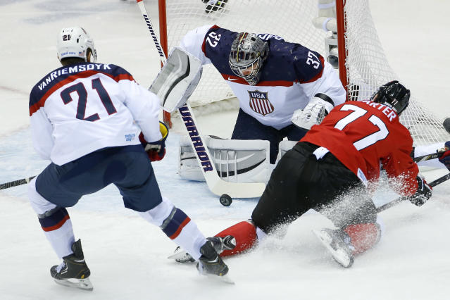 Canada forward Jeff Carter shoots on USA goaltender Jonathan Quick as USA forward James van Riemsdyk skates in to help protect the goal during the first period of the men's semifinal ice hockey game at the 2014 Winter Olympics, Friday, Feb. 21, 2014, in Sochi, Russia. (AP Photo/Matt Slocum)