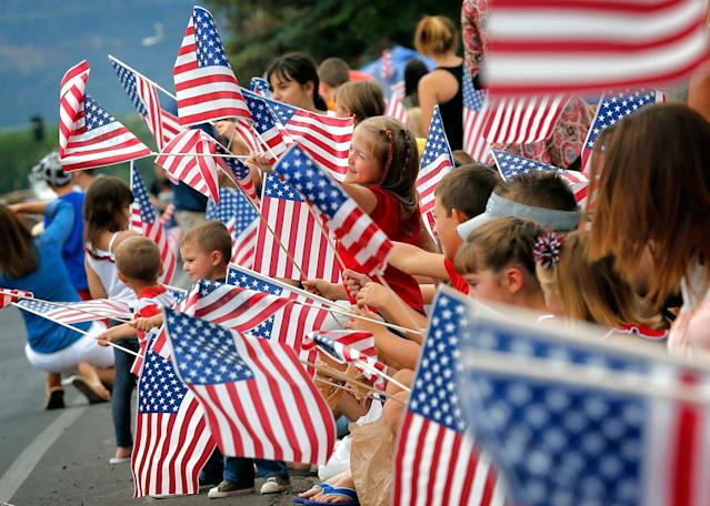 <p>People wave flags as the Independence Day parade rolls down Main Street, Friday, July 4, 2014, in Eagar, Ariz. The Northern Arizona town celebrates the Fourth of July annually with a parade and fireworks. (Photo: Matt York/AP) </p>