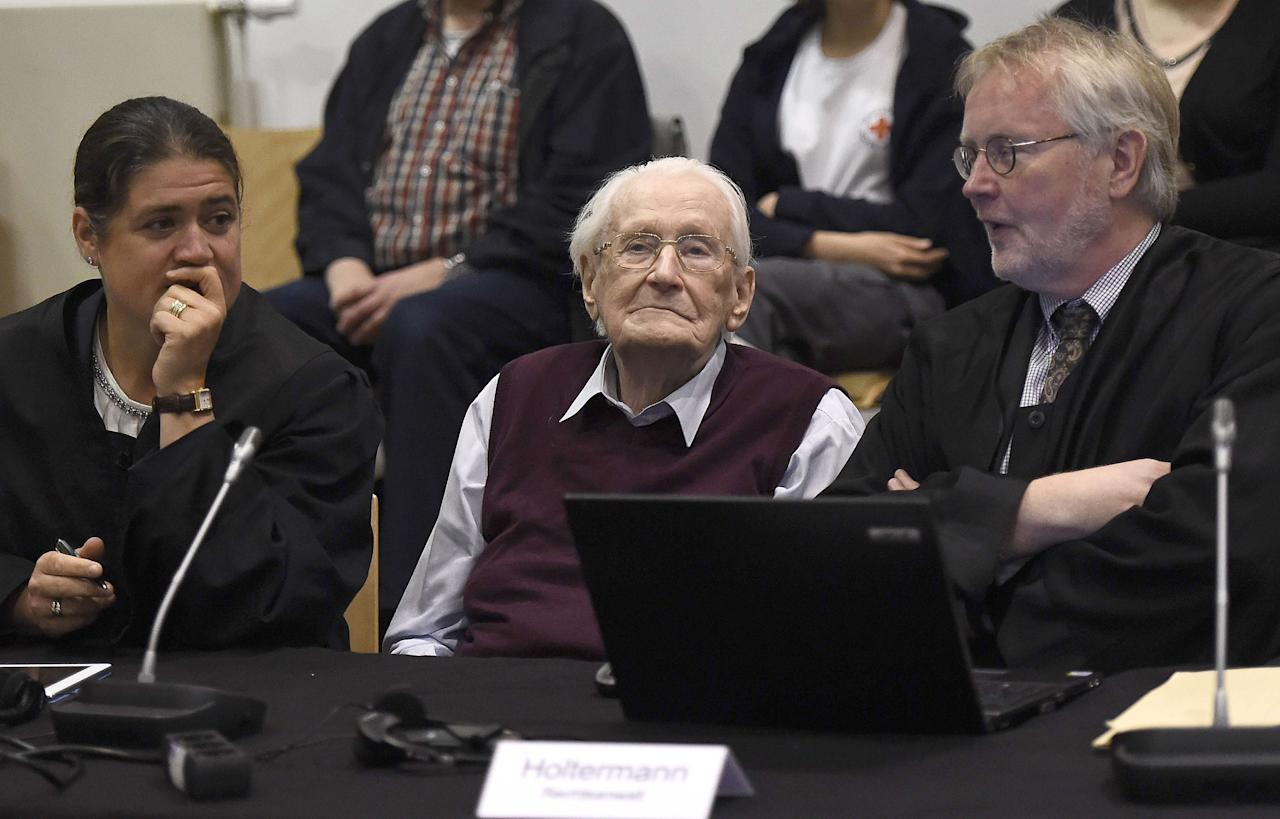 """Oskar Groening (C), defendant and former Nazi SS officer dubbed the """"bookkeeper of Auschwitz"""", reacts as he sits between his lawyers Hans Holtermann (R) and Susanne Frangenberg (L) in the courtroom during the verdict of his trial in Lueneburg, Germany, July 15, 2015. The 94-year-old German man who worked as a bookkeeper at the Auschwitz death camp was convicted on Wednesday of being an accessory to the murder of 300,000 people and was sentenced to four years in prison, in what could be one of the last big Holocaust trials. REUTERS/Axel Heimken/Pool"""