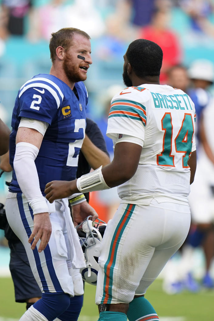 Miami Dolphins quarterback Jacoby Brissett (14) and Indianapolis Colts quarterback Carson Wentz (2) meet at the end of an NFL football game, Sunday, Oct. 3, 2021, in Miami Gardens, Fla. The Colts defeated the Dolphins 27-17. (AP Photo/Wilfredo Lee)