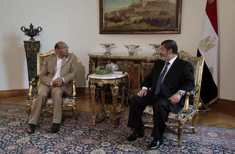 Tunisian President Moncef Marzouki, left, meets with Egyptian President Mohammed Morsi, right, at the Presidential palace in Cairo, Egypt, Friday, July 13, 2012. The presidents of Egypt and Tunisia pledge to open a new chapter in relations following uprisings that overthrew longtime rulers, replacing them with a Muslim Brotherhood figure and an activist who was exiled.(AP Photo/Maya Alleruzzo)