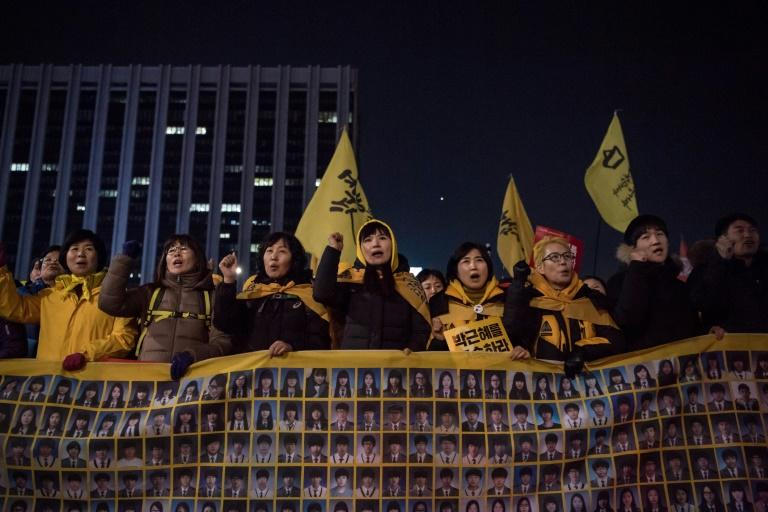 Relatives of victims of the 2014 Sewol ferry disaster join anti-government activists during a rally in Seoul on March 4, 2017