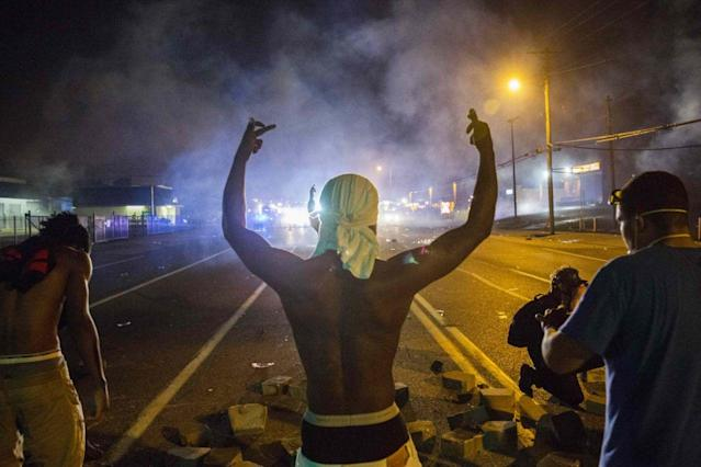 <p>Demonstrators face off with police after tear gas was fired at protesters reacting to the shooting of Michael Brown in Ferguson, Missouri August 17, 2014. (Lucas Jackson/Reuters) </p>