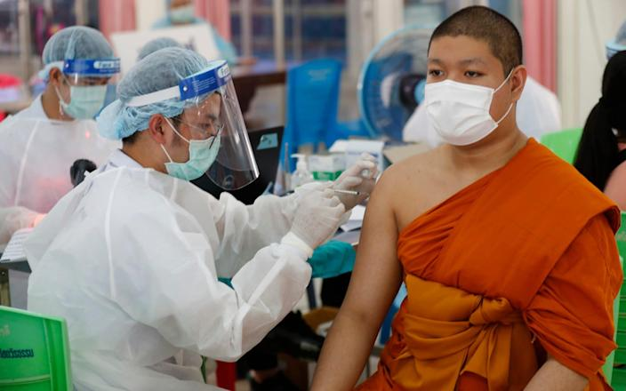 A health worker injects a Buddhist monk with dose of the Sinovac COVID-19 vaccine in Bangkok, Thailand - Sakchai Lalit / AP