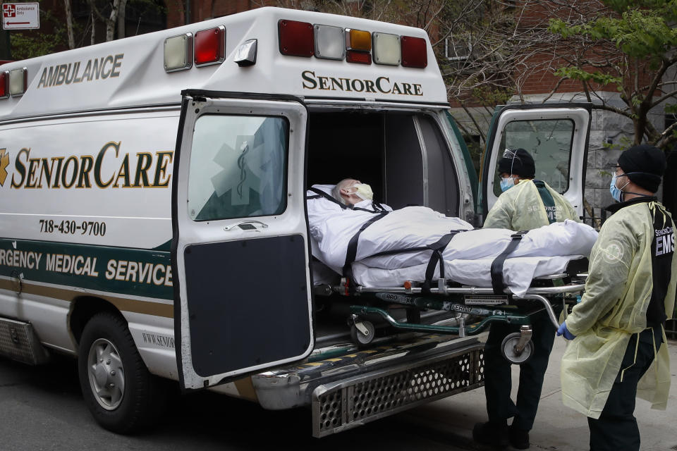 FILE - In this April 17, 2020, file photo, a patient is loaded into an ambulance by emergency medical workers outside Cobble Hill Health Center in the Brooklyn borough of New York. More than 9,000 recovering coronavirus patients in New York state were released from hospitals into nursing homes at the height of the pandemic under a controversial order that was scrapped amid criticisms it accelerated outbreaks, according to new records obtained by The Associated Press. (AP Photo/John Minchillo, File)