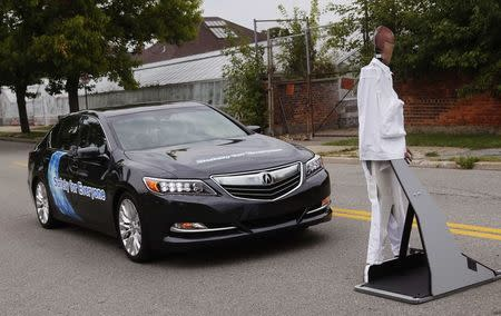 An Acura RLX sedan brakes to avoid a mannequin during Honda's Omni Directional V2X demo at the ITS World Congress in Detroit