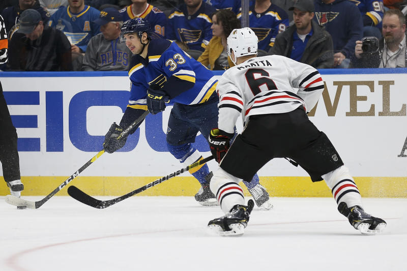 St. Louis Blues' Jordan Kyrou (33) handles the puck as Chicago Blackhawks' Olli Maatta (6), of Finland, defends during the second period of an NHL hockey game Tuesday Feb. 25, 2020, in St. Louis. (AP Photo/Scott Kane)