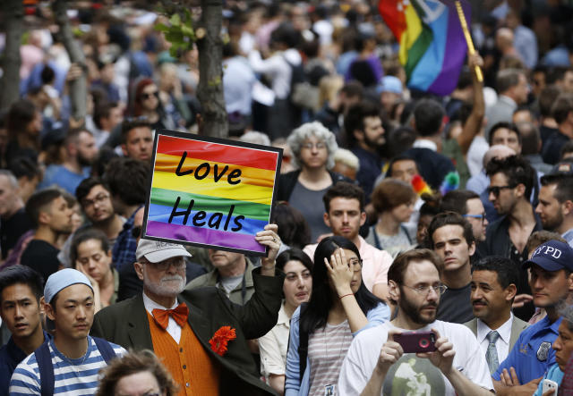 <p>A man walks through the crowd holding a sign during a vigil and memorial for victims of the Orlando nightclub shootings near the historic Stonewall Inn, a gay bar, on Monday, June 13, 2016, in New York. (Photo: Kathy Willens/AP) </p>