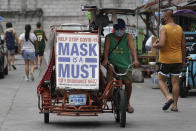 A man rides his pedicab with a slogan to remind people to wear masks to prevent the spread of the coronavirus in Manila, Philippines on Monday, April 26, 2021. COVID-19 infections in the Philippines surged past 1 million Monday in the latest grim milestone as officials assessed whether to extend a monthlong lockdown in Manila and outlying provinces amid a deadly spike or relax it to fight recession, joblessness and hunger. (AP Photo/Aaron Favila)