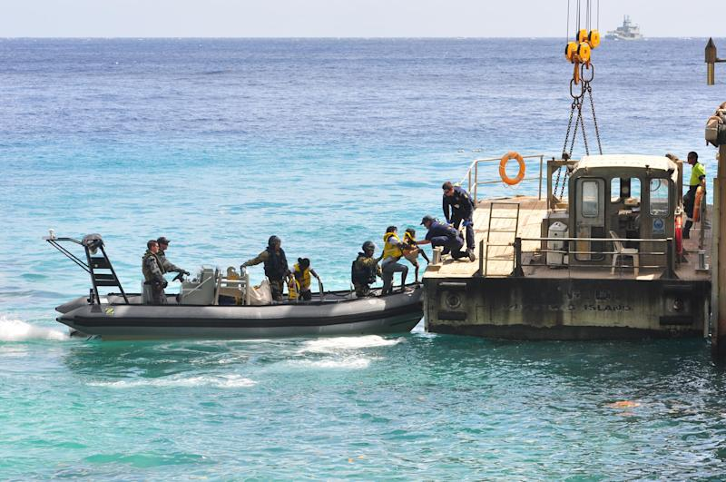 Suspected asylum seekers arrive at Christmas Island after being intercepted and escorted in by the Australian Navy - getty