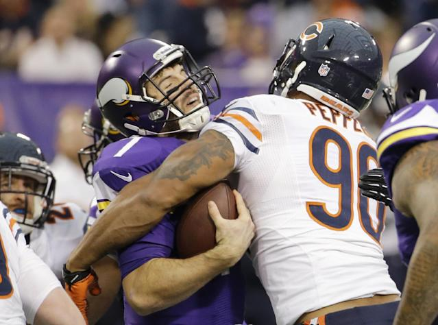 Minnesota Vikings quarterback Christian Ponder, left, is sacked by Chicago Bears defensive end Julius Peppers during the first half of an NFL football game Sunday, Dec. 1, 2013, in Minneapolis. (AP Photo/Ann Heisenfelt)
