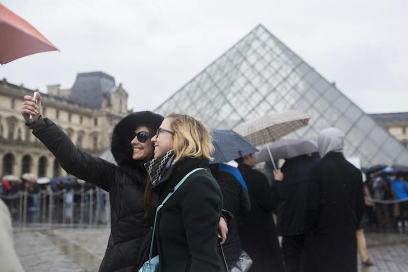 """Two women take a selfie, as they wait to enter the re-opened Louvre museum, a day after a man attacked French soldiers near the museum in Paris, Saturday, Feb. 4, 2017. The Louvre in Paris reopened to the public Saturday morning, less than 24-hours after a machete-wielding assailant shouting """"Allahu Akbar!"""" was shot by soldiers, in what officials described as a suspected terror attack. (AP Photo/Kamil Zihnioglu)"""