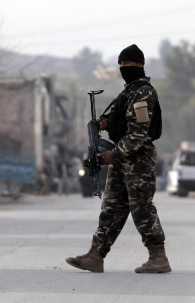 A security official stands guard at the scene of a suicide car bomb attack which killed and injured several people at the National Directorate of Security in Jalalabad, Afghanistan, Sunday, Feb 24, 2013. A series of early morning attacks hit eastern Afghanistan Sunday, with three separate suicide bombings in outlying provinces and a shootout between security forces and a would-be attacker in the capital city of Kabul. (AP Photo/Rahmat Gul)
