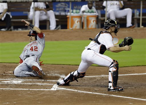 Washington Nationals' Ian Desmond slides into home plate as Miami Marlins catcher Rob Brantly waits for the throw during the first inning of a baseball game, Monday, April 15, 2013 in Miami. Desmond and Ryan Zimmerman scored on a single by Tyler Moore. (AP Photo/Wilfredo Lee)