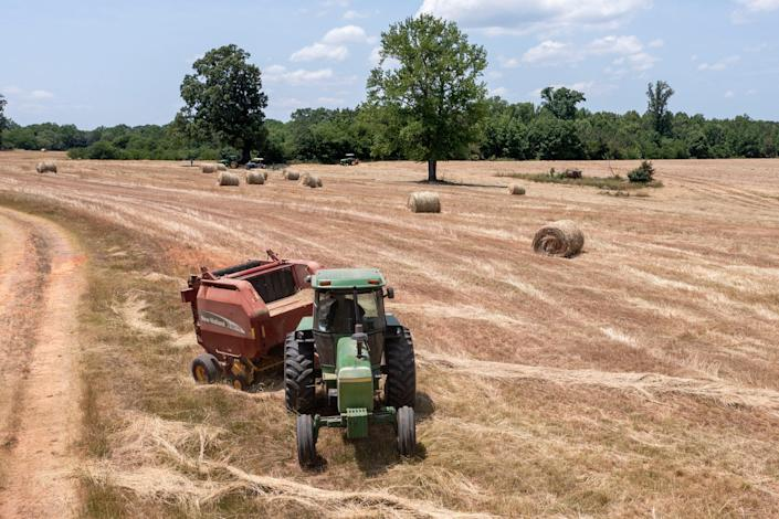John Boyd runs a hay baler at his farm in Boydton, Va., on May 27. Two generations out of slavery, Black farmers had amassed more than 16 million acres of land by 1910 and made up about 14% of farmers. The fruit of their labors fed much of America. In 2021, they have fewer than 4.7 million acres.