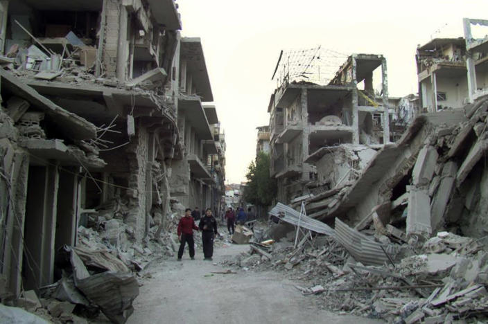 In this citizen journalism image provided by the Homs City Union of The Syrian Revolution, which has been authenticated based on its contents and other AP reporting, Syrian citizens walk in a destroyed street that was attacked on Wednesday by Syrian forces warplanes, at Abu al-Hol street in Homs province, Syria, Thursday Nov. 29, 2012. Two US-based Internet-monitoring companies say Syria has shut off the Internet nationwide. Activists in Syria reached Thursday by satellite telephone confirmed the unprecedented blackout, which comes amid intense fighting in the capital, Damascus.(AP Photo/Homs City Union of The Syrian Revolution)