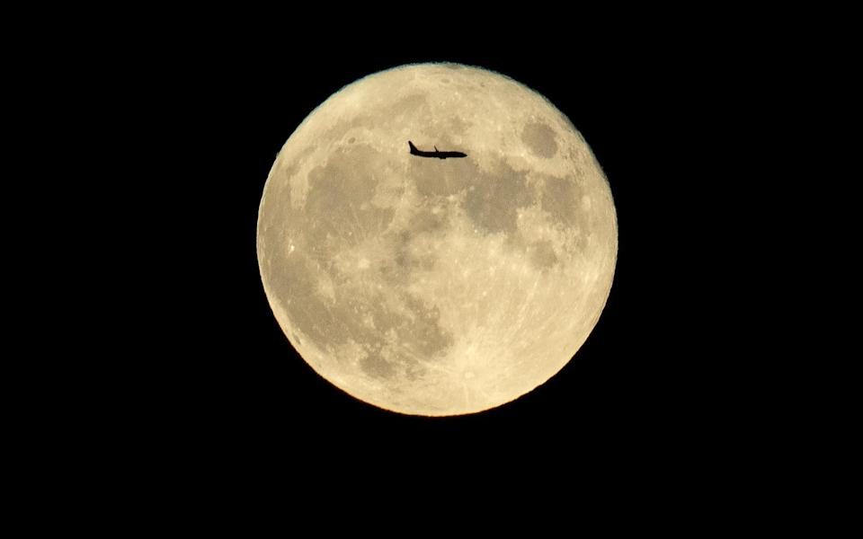 As China celebrates Mid-Autumn Festival – also known as Moon Festival or Mooncake Festival – a plane is seen crossing the moon in Beijing. - AFP via Getty Images