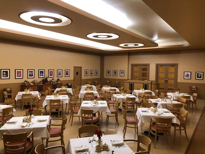 """<div class=""""caption""""> The movie studio commissary in <em>Hollywood</em> features refurbished chairs from the real Warner Bros. studios. </div> <cite class=""""credit"""">Courtesy of Netflix</cite>"""