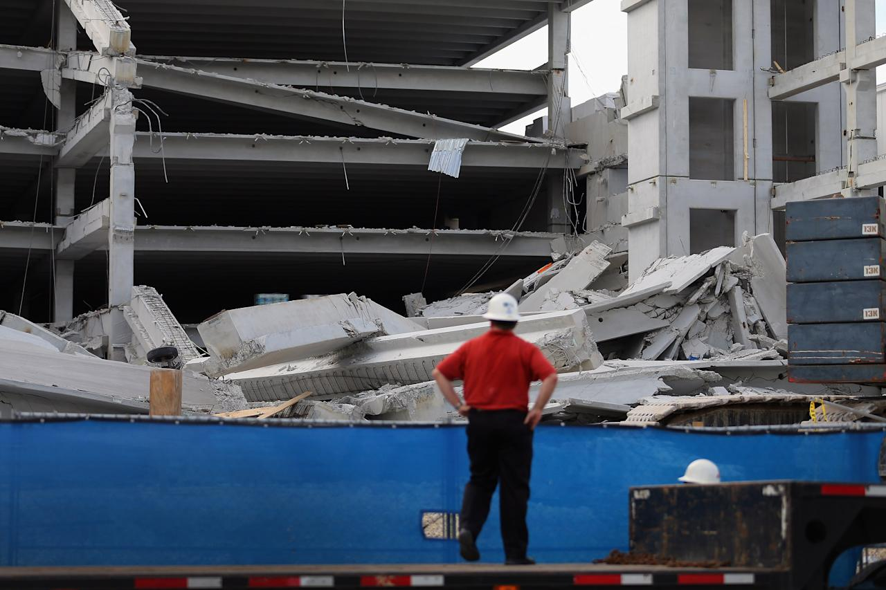 DORAL, FL - OCTOBER 10:  A person looks on from a flat bed truck at the rubble of a four-story parking garage that was under construction and collapsed at the Miami Dade College's West Campus on October 10, 2012 in Doral, Florida.  Early reports indicate that one person was killed, at least seven people injured and one is still trapped.  (Photo by Joe Raedle/Getty Images)