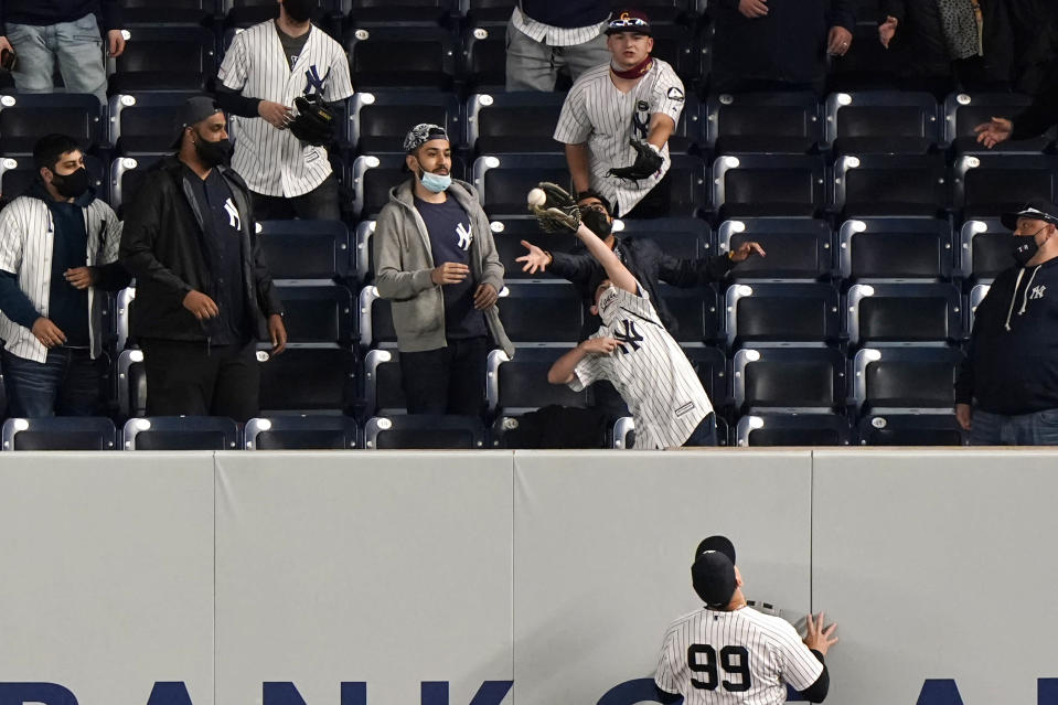 New York Yankees right fielder Aaron Judge (99) watches a fan grab a home run hit by Baltimore Orioles Rio Ruiz during the ninth inning of a baseball game, Tuesday, April 6, 2021, at Yankee Stadium in New York. (AP Photo/Kathy Willens)