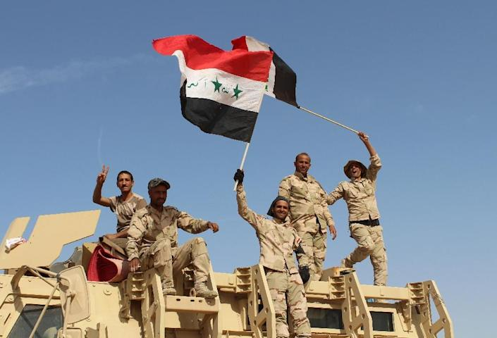 Iraqi government forces celebrate on March 10, 2016 after retaking the town of Zankura, northwest of Ramadi, from IS in Anbar province (AFP Photo/Moadh Al-Dulaimi)