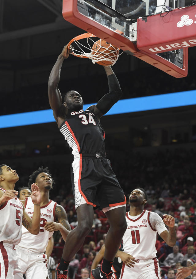 Georgia forward Derek Ogbeide (34) dunks the ball over Arkansas defenders Jalen Harris (5), Gabe Osabuohien (22) and Keyshawn Embery-Simpson (11) during the second half of an NCAA college basketball game, Tuesday, Jan.29, 2019 in Fayetteville, Ark. (AP Photo/Michael Woods)
