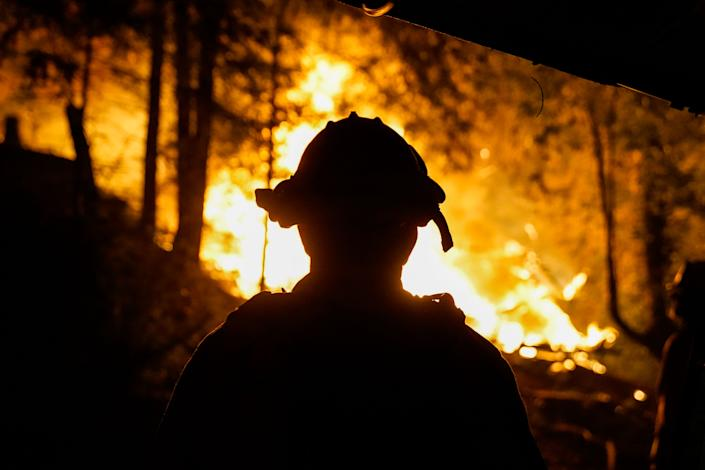 Firefighters respond to a structure fire along Riverdale Boulevard as the fire line creeps up on Highway 9 in Boulder Creek, Calif. (Kent Nishimura/Los Angeles Times via Getty Images)