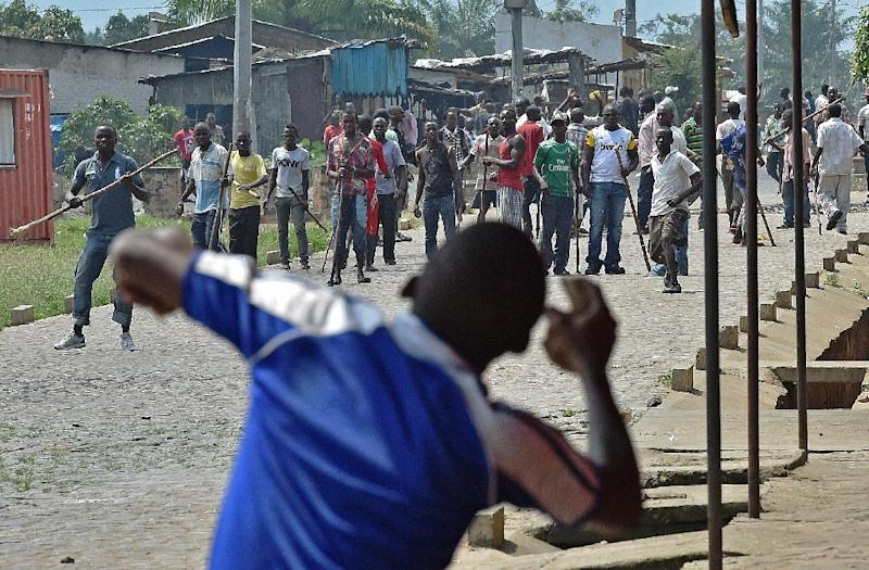 A protestor opposed to the Burundian President's third term throws a rock at members of the Imbonerakure, the youth wing of the ruling party, armed with sticks in the Kinama neighborhood of Bujumbura on May 25, 2015