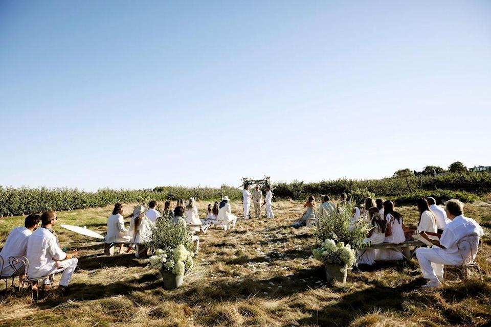 """""""Each family and group of friends got their own bench separated from others to maintain social separation,"""" Dean says. """"Giant floral arrangements by Missie Flowers anchored the entrance to the aisle."""""""