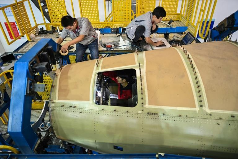 Employees work on an aft fuselage section of a C919