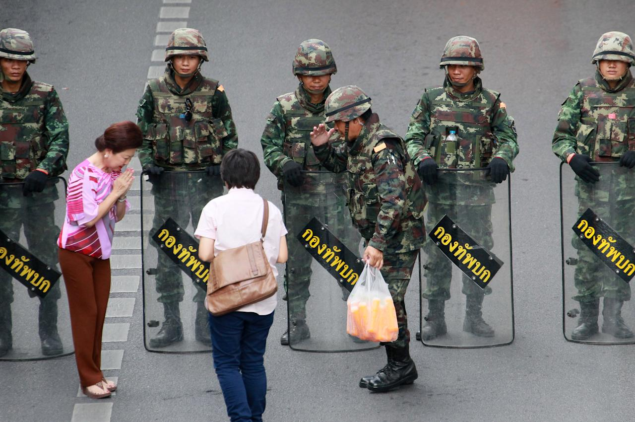 Well-wishers hand cold drinks to Thai soldiers securing the area to prevent an anti-coup demonstration at Victory Monument in Bangkok, Thailand Thursday, May 29, 2014. Hundreds of Thai troops and police sealed off one of Bangkok's busiest intersections Thursday in an attempt to block a planned protest one week after a military coup. (AP Photo/Wason Wanichakorn)