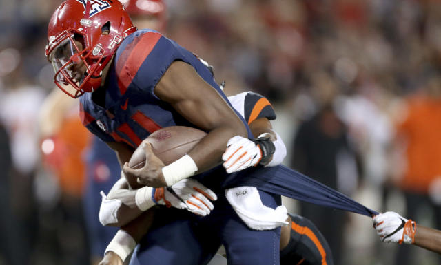 "Arizona quarterback <a class=""link rapid-noclick-resp"" href=""/ncaaf/players/263219/"" data-ylk=""slk:Khalil Tate"">Khalil Tate</a> (14) drags a couple of Oregon State defenders into the end zone on a touchdown run during the second quarter of an NCAA college football game Saturday, Nov. 11, 2017, Tucson, Ariz. (Kelly Presnell/Arizona Daily Star via AP)"