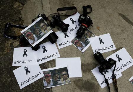 Colombian photographers leave the cameras on the floor in front of the Ecuadorean embassy to protest against the murder of journalist Javier Ortega, photographer Paul Rivas and their driver Efrain Segarra in Bogota, Colombia April 16, 2018. Picture taken April 16, 2018. REUTERS/Jaime Saldarriaga