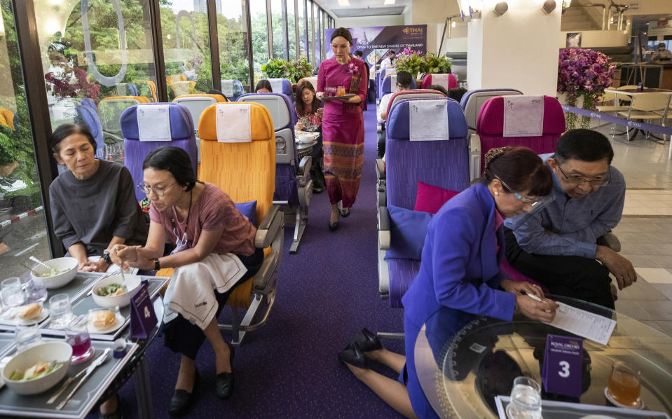 A flight attendant serves welcome drinks in a flight-themed restaurant at the Thai Airways head office in Bangkok, Thailand on Oct. 3, 2020. The airline is selling time on its flight simulators to wannabe pilots while its catering division is serving meals in a flight-themed restaurant complete with airline seats and attentive cabin crew. The airline is trying to boost staff morale, polish its image and bring in a few pennies, even as it juggles preparing to resume international flights while devising a business reorganization plan. (AP Photo/Sakchai Lalit)