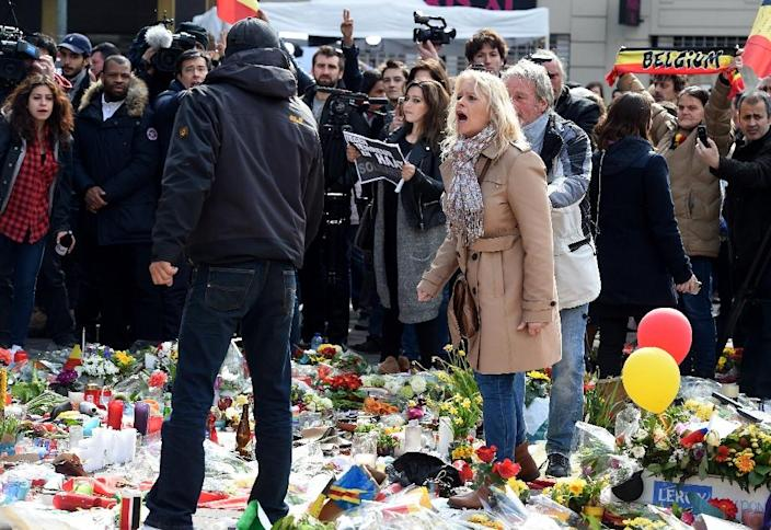 A woman shouts at a man walking amongst floral tributes in area outside the Stock Exchange in Brussels, on March 27, 2016 (AFP Photo/Patrick Stollarz)