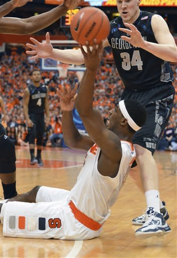 Syracuse's C.J. Fair looks for help as Georgetown's Nate Lubick, right, moves in during the first half of an NCAA college basketball game in Syracuse, N.Y., Saturday, Feb. 23, 2013. (AP Photo/Kevin Rivoli)