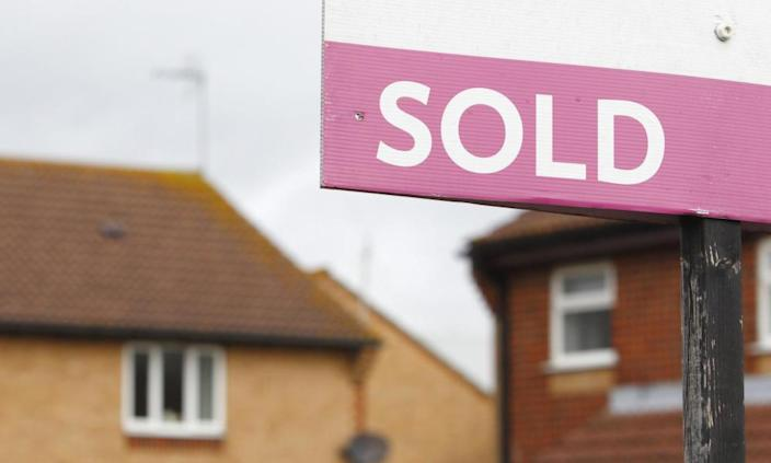 A sold sign with properties in the background